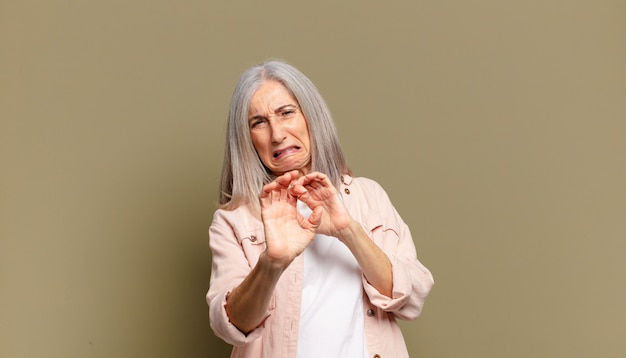 Senior woman feeling disgusted and nauseous, backing away from something nasty, smelly or stinky, saying yuck