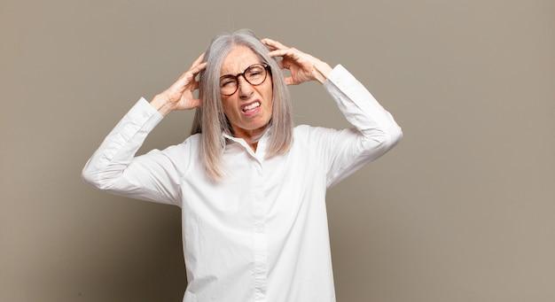 欲求不満とイライラ、失敗にうんざりしている、退屈で退屈な仕事にうんざりしている年配の女性