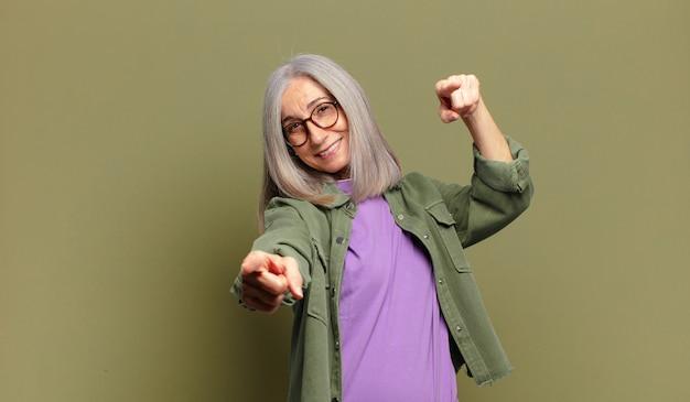 행복하고 자신감을 느끼고, 양손으로 정면을 가리키고 웃고, 당신을 선택하는 고위 여자