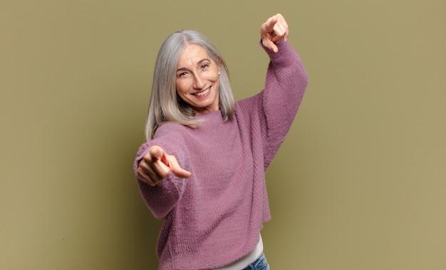 Старшая женщина чувствует себя счастливой и уверенной, указывая обеими руками и смеясь, выбирая вас