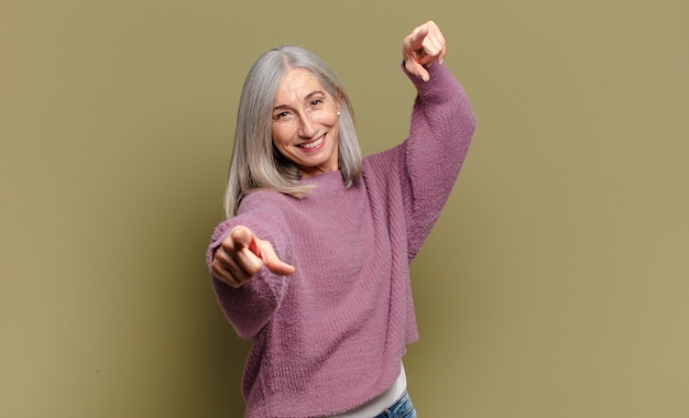 Senior woman feeling happy and confident, pointing with both hands and laughing, choosing you