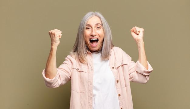 Старшая женщина чувствует себя счастливой, позитивной и успешной, празднует победу, достижения или удачу