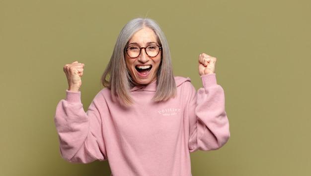 Старшая женщина чувствует себя счастливой, удивленной и гордой, кричит и празднует успех с широкой улыбкой