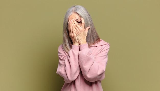 Старшая женщина чувствует себя напуганной или смущенной, подглядывает или шпионит с полузакрытыми руками глазами
