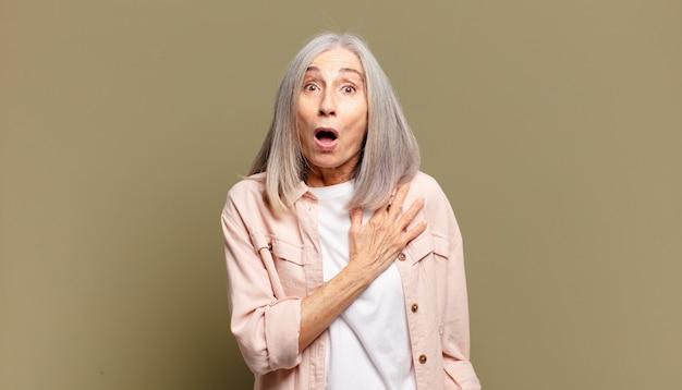 ショックを受けて驚いた年配の女性、笑顔、心に手を差し伸べる、一人になって幸せ、または感謝の気持ちを示す