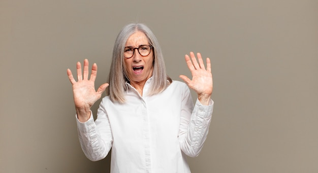 Старшая женщина чувствует себя ошеломленной и напуганной, боится чего-то пугающего, с открытыми руками говорит: «держись подальше»