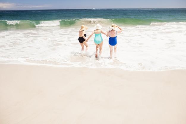 Senior woman friends running into water