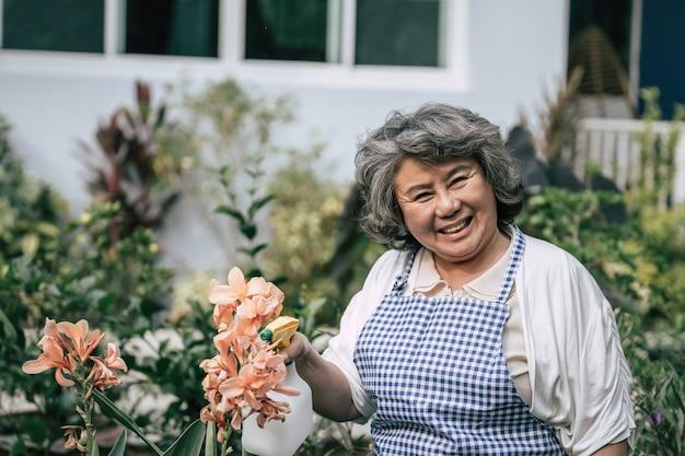 Пожилая женщина собирает цветы в саду
