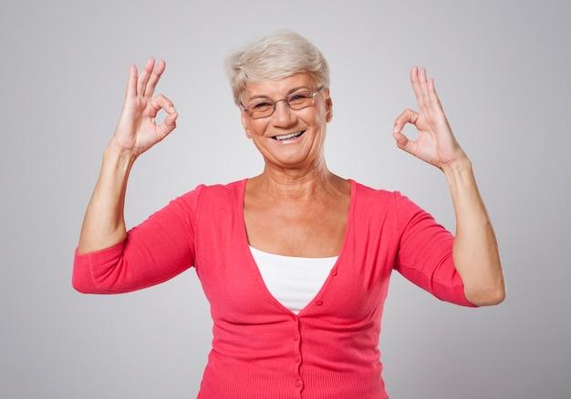 Donna maggiore che gesturing segno giusto