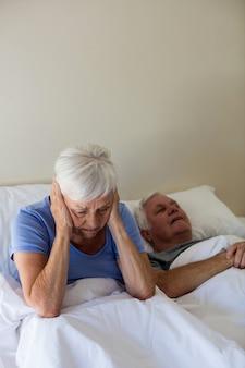 침실에 침대에서 코골이 남자와 방해 받고 고위 여자
