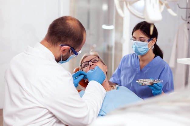 椅子に座っている歯科医と看護師から口腔病治療を受けている年配の女性。オレンジ色の機器を備えた歯科医院の歯科医による診察中の高齢患者。