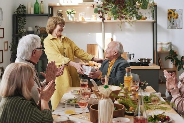 友人にプレゼントを贈り、友人との休日の夕食時に誕生日を祝う年配の女性