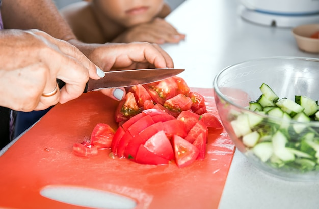 Senior woman grandmother cooking healthy salad for grandson. grandma cutting tomato by knife on cutting board for dinner.