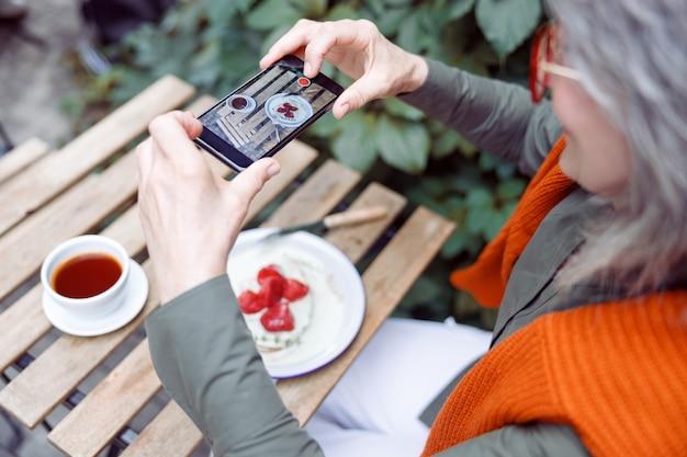 수석 여성 손님은 야외 테이블에서 스마트폰으로 딸기 디저트 사진을 찍는다