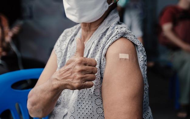 엄지손가락을 치켜드는 고위 여성의 손이 붕대로 코로나바이러스 covid19 어깨에 예방접종을 하러 갔다