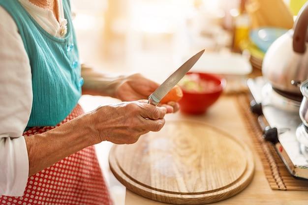 年配の女性が台所の木の板に野菜を刻んで手