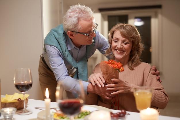 Старшая женщина счастлива с цветами во время романтического ужина с мужем дома