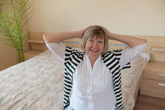 Старший женщина счастлива с седыми волосами расслабляющий улыбается смотрит в камеру в ее доме в спальне.