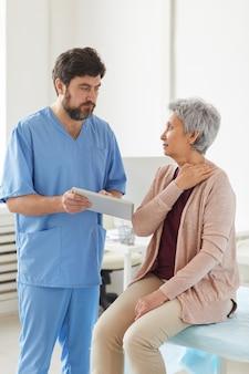 年配の女性が医者のオフィスを訪れ、医者がタブレットpcを使用しているときに首の痛みを訴えました