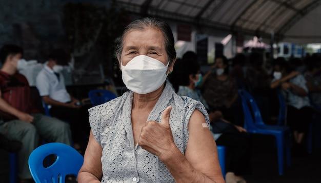 수석 여성은 엄지손가락을 보여주는 석고와 함께 코로나바이러스 covid19 어깨에 예방 접종을 하러 갔다
