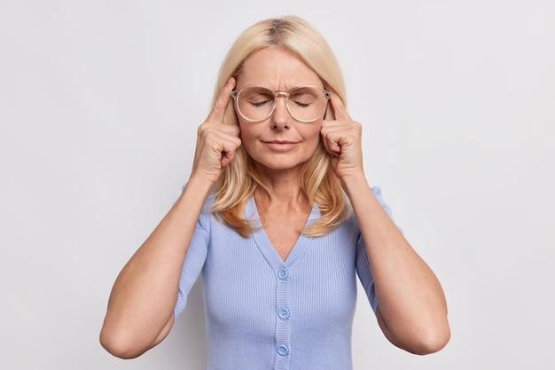 年配の女性は頭痛が目を閉じて寺院に触れ、緊張した顔は痛みを伴う片頭痛に苦しんでいます大きな眼鏡をかけ、白い壁の上に隔離された青いジャンパーが焦点を合わせようとします