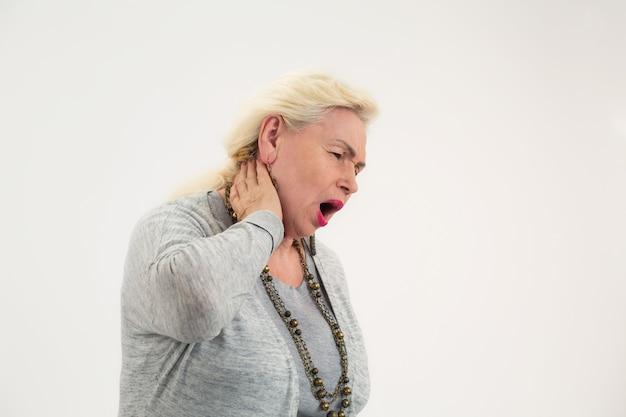 고위 여성은 긴장된 근육으로 인한 목 고립 통증을 만지는 목 통증 여성이 있습니다