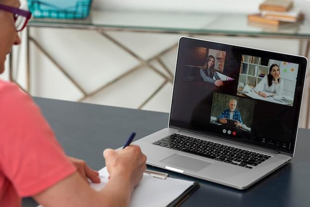 自宅のラップトップでビデオ通話をしている年配の女性