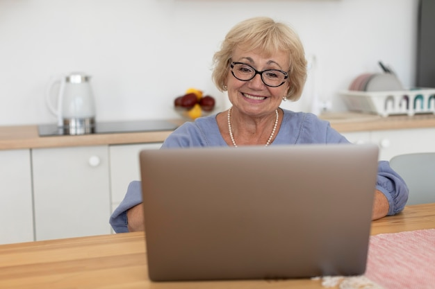 Старшая женщина, имеющая видеозвонок со своей семьей