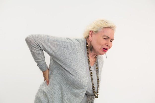 Старшая женщина, имеющая боль в спине, изолировала леди, касаясь ее спины, как вылечить люмбаго
