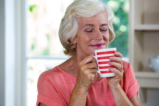 Senior woman having coffee at home