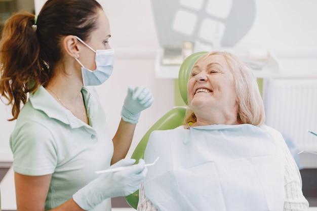 歯科医院で歯科治療を受けている年配の女性。女性は歯の治療を受けています