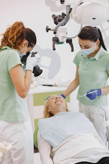 Senior donna con trattamento dentale presso l'ufficio del dentista. il dottore fa una foto dei denti del paziente.