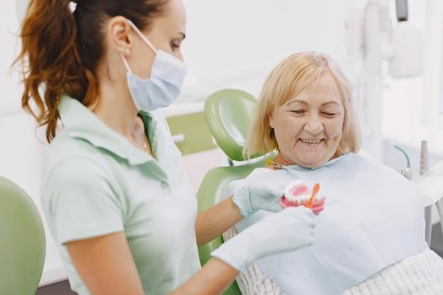 Senior donna con trattamento dentale presso l'ufficio del dentista. la donna è in cura per i denti