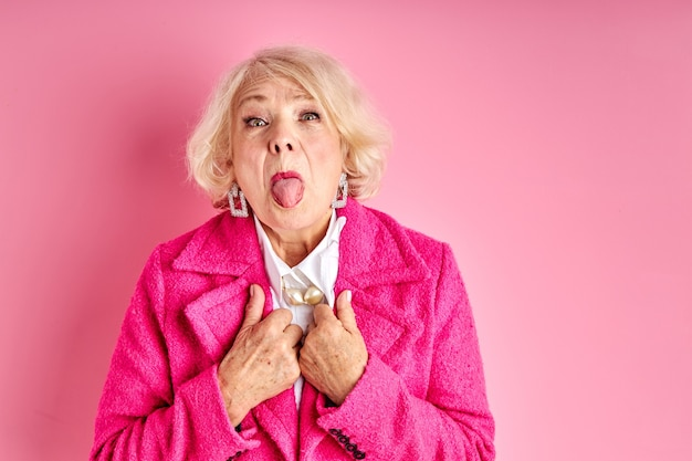 Senior woman having fun at free time leisure, showing tongue at camera, crazy woman in pink stylish coat isolated on pink space