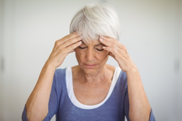 Старшая женщина с головной болью