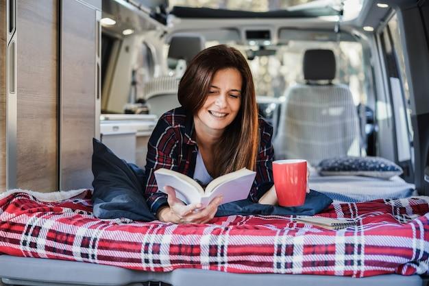 Старшая женщина, имеющая внутри автофургона, читает книгу и пьет кофе - фокус на лице