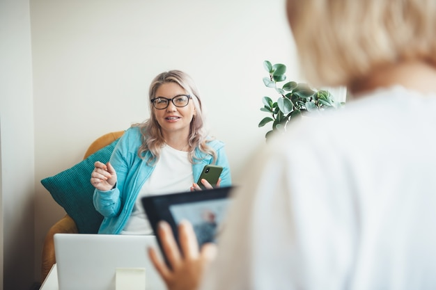 Senior woman having a meeting at home while using a laptop and wear eyeglasses