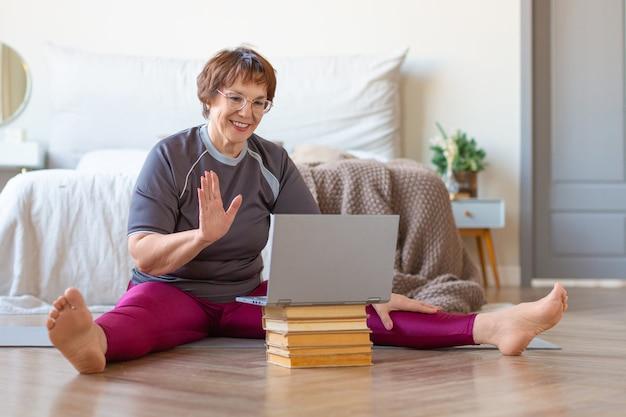 ピラティストレーニングの前にオンラインでトレーナーとオンラインミーティングをしている年配の女性。老後の健康的でアクティブなライフスタイルの概念。