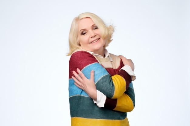 自分を抱きしめる幸せな表情を満足している年配の女性