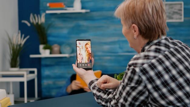 거실에 앉아 스마트 폰을 사용하여 조카와 화상 통화 온라인 대화를하는 고위 여자