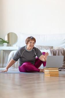 ピラティストレーニングの前にオンラインでトレーナーとビデオ会話をしている年配の女性。彼女は挨拶し、ラップトップで手を振っています。老後の健康的でアクティブなライフスタイルの概念。
