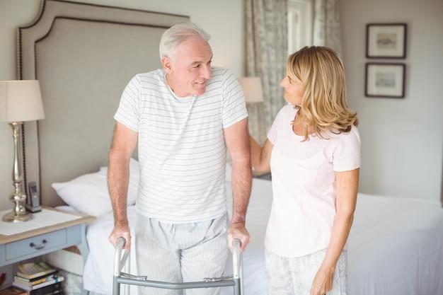 Старшая женщина помогает мужчине ходить с ходунками