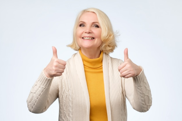 Senior woman in her 70s showing thumbs up gestures with both hands,
