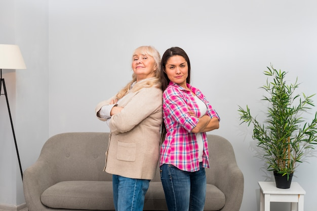 Senior woman and her adult daughter standing back to back at home