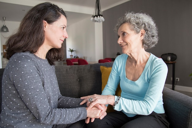 Senior woman and her daughter talking and holding hands
