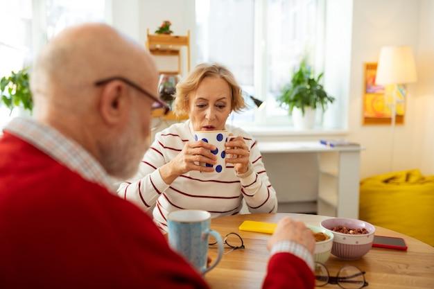 テーブルで彼女の友人の向かいに座っている間おいしいお茶とカップを保持している年配の女性