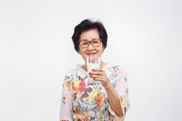 白い背景で隔離のミルクのガラスを保持している年配の女性。
