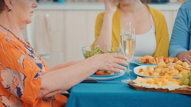 グラスワインを持っている年配の女性、家族で楽しい時間を過ごしている若い幸せなカップル。多世代、4人、2人の幸せなカップルがグルメディナーの最中に話したり食事をしたり、ホームでの時間を楽しんだりします。 Premium写真