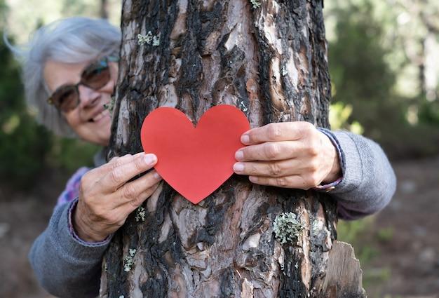 木の幹にハート型の紙を持って、森林破壊の概念から木を救う年配の女性