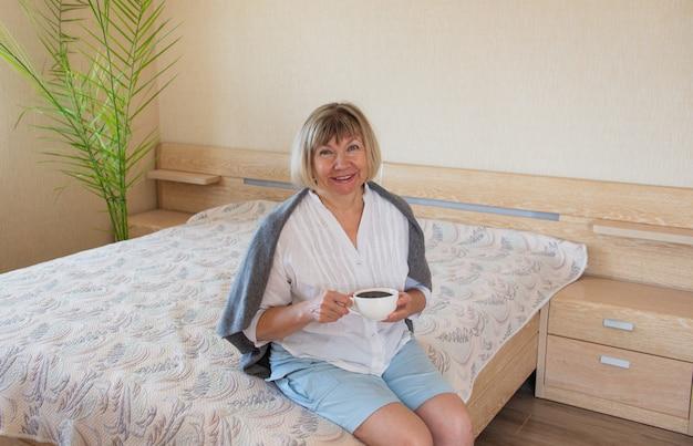 Старший женщина, держащая кружку кофе расслабляющий, улыбаясь в своем доме в спальне. доброе утро концепция, проснись